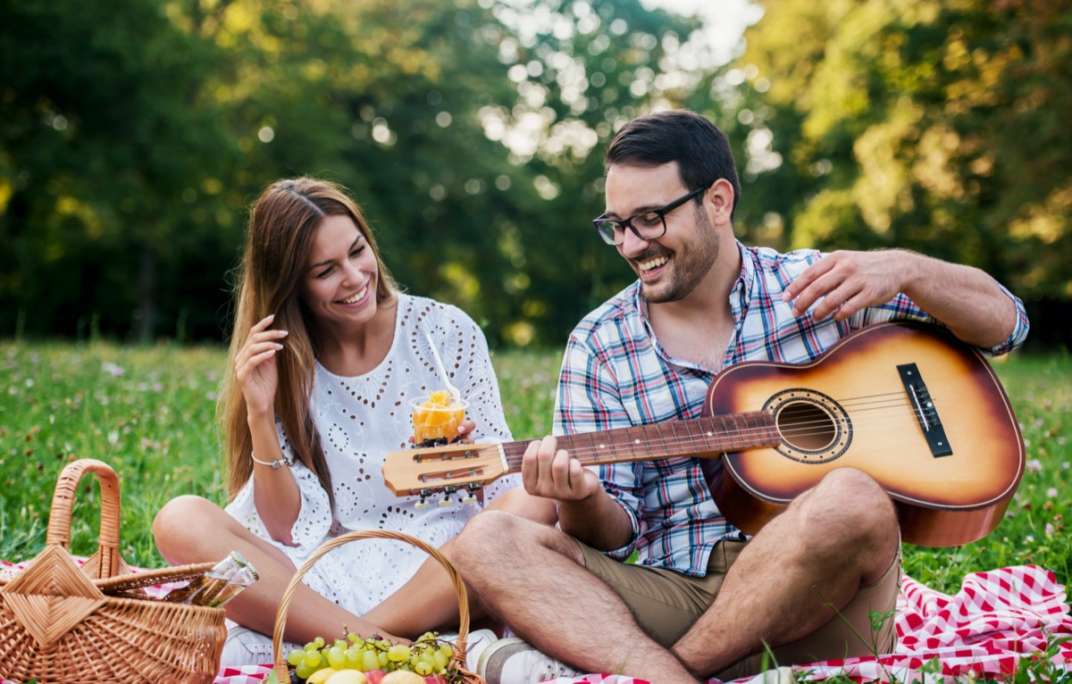 Young couple having fun on picnic in the park