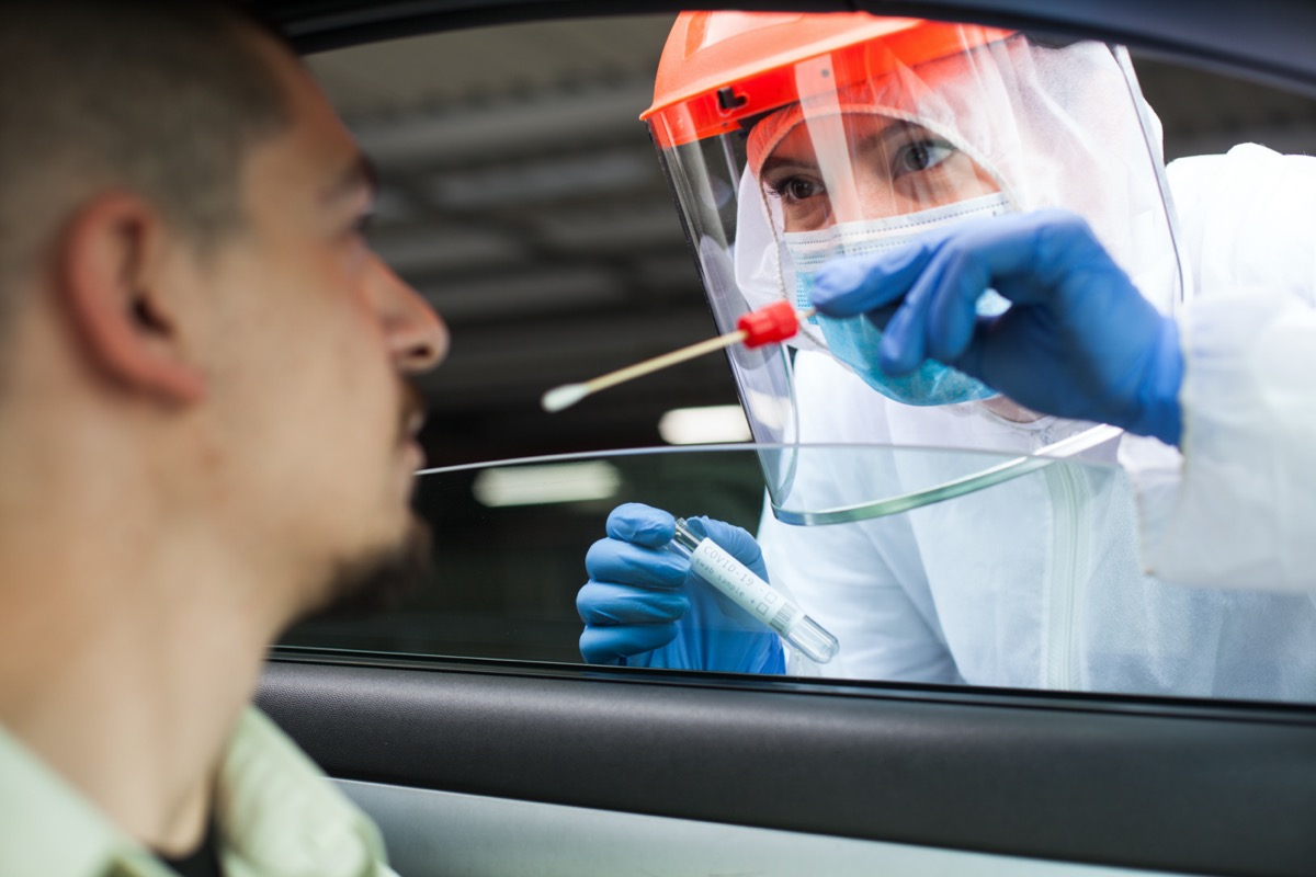Medical worker performing drive-thru COVID-19 test,taking nasal swab specimen sample from male patient through car window.