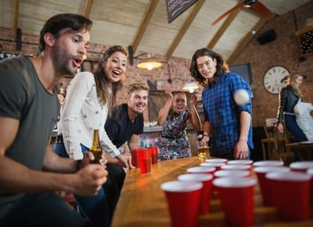 Young friends enjoying beer pong game on table in restaurant