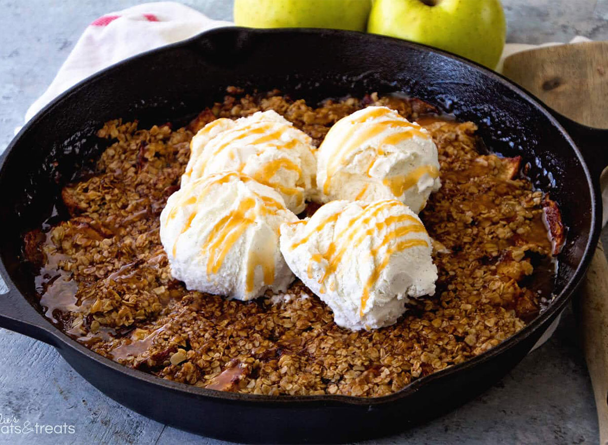 grilled caramel apple crisp in skillet topped with ice cream