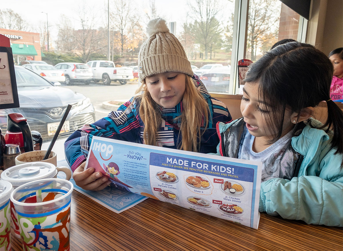 two kids looking at ihop menu