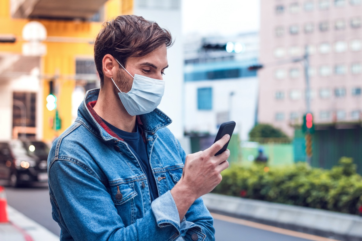 man with a beard chats on his phone and wears a face pollution mask to protect himself from coronavirus.