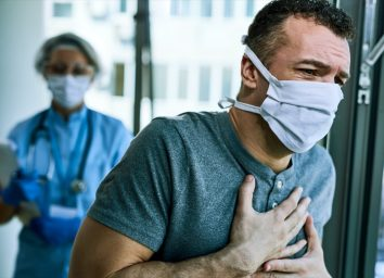 Male patient wearing face mask and feeling chest pain while being at the hospital during coronavirus epidemic
