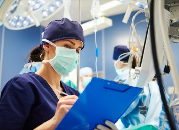 Female nurse examining all the parameters in operating room