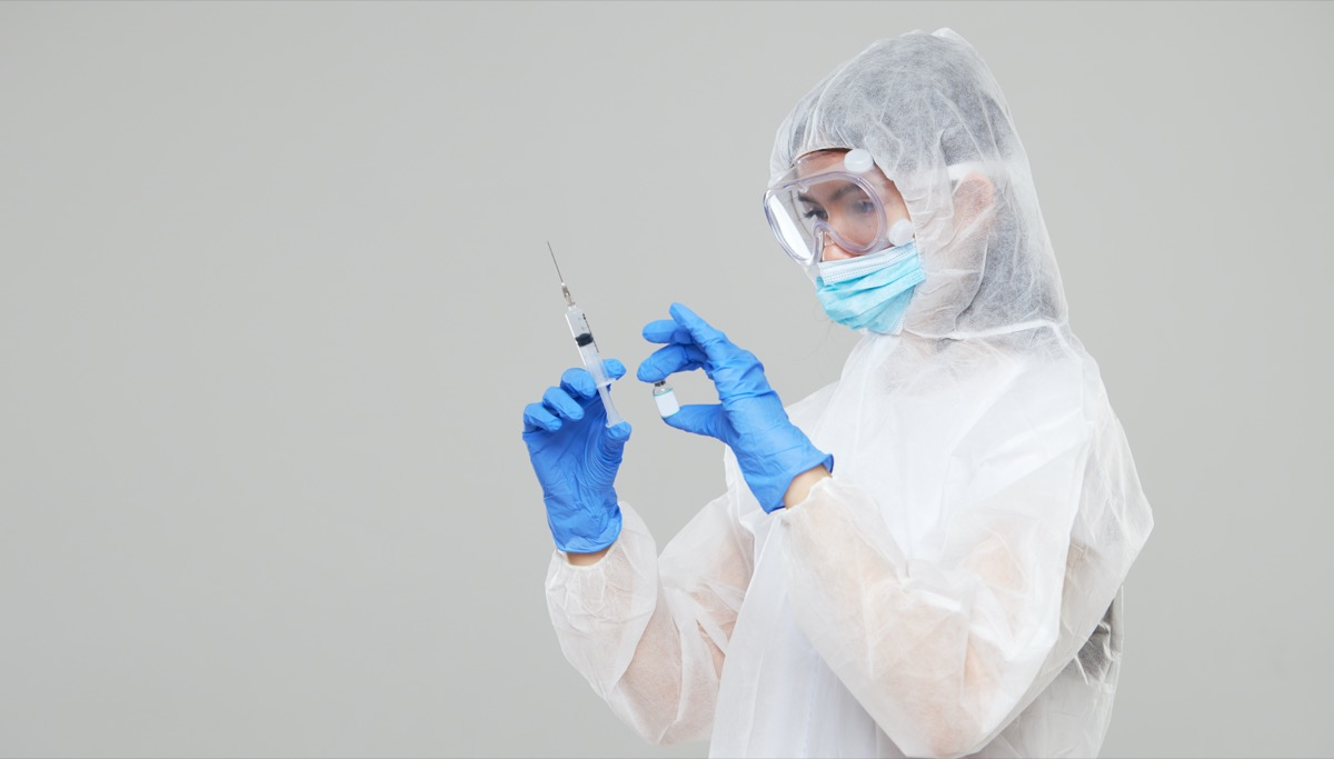 An asian woman in a protective suit and mask holds an injection syringe and vaccine
