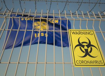 Biohazard coronavirus sign on the barbed wire fence near flag of Oregon.