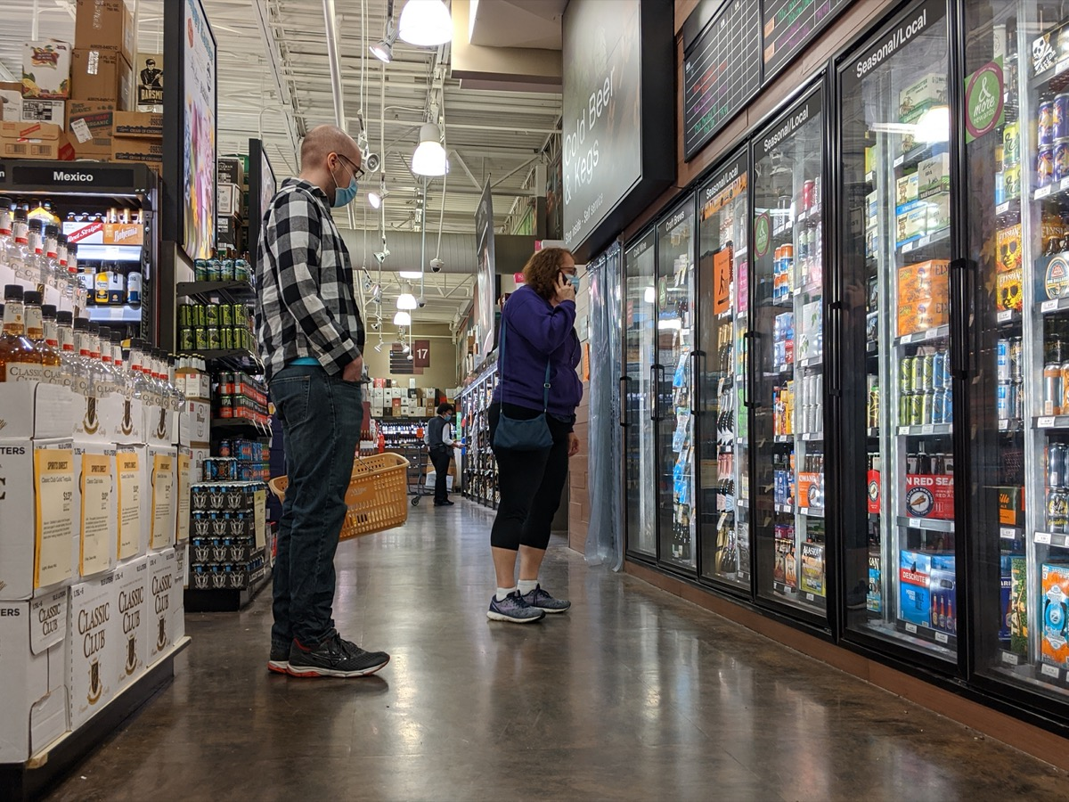 People wearing face masks while shopping for beer and liquor inside a Total Wine and More beverage shop in downtown Bellevue