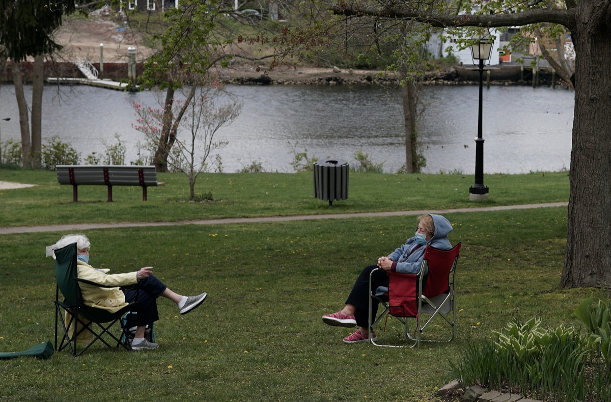 Two masked elderly women maintain social distancing during their conversation in the park
