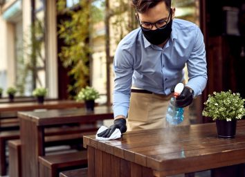 Waiter wearing protective face mask while disinfecting tables at outdoor cafe