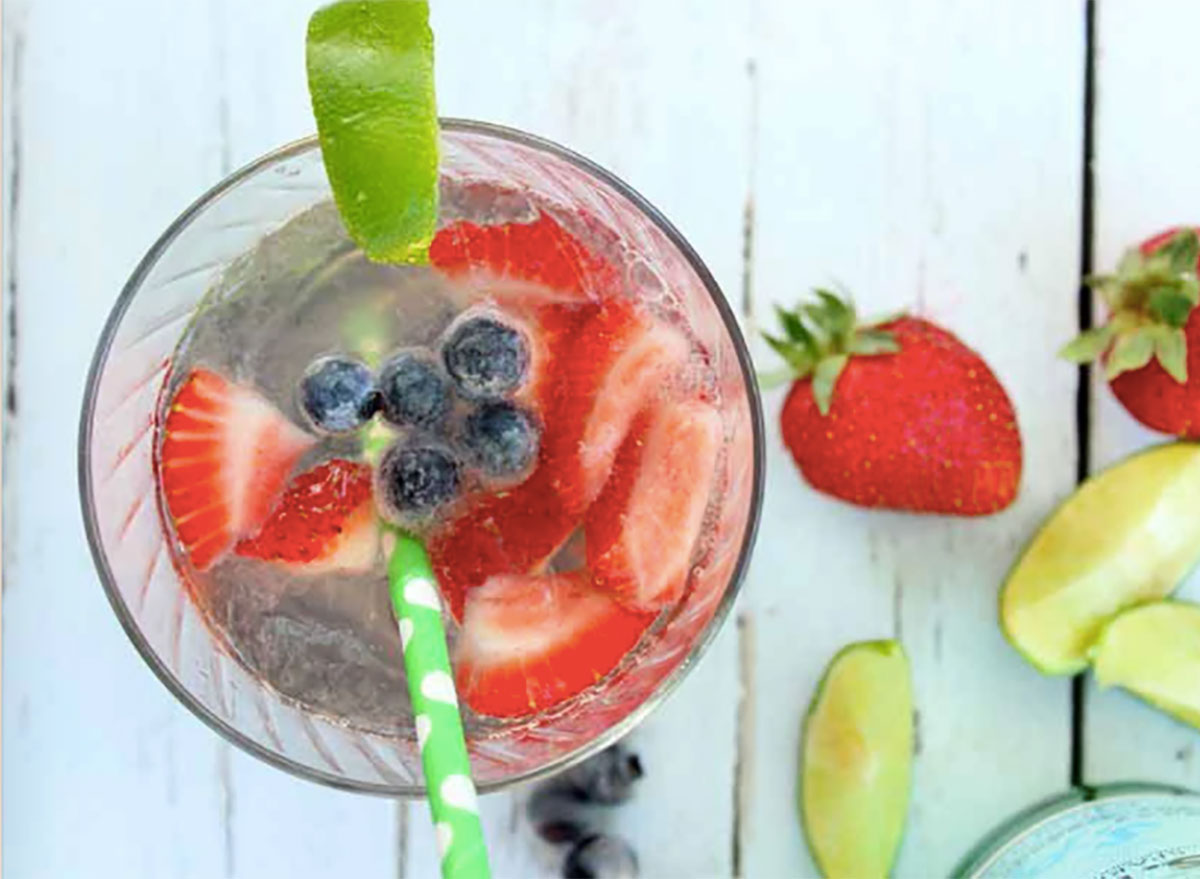 skinny summer cocktail with strawberries and lime wedges
