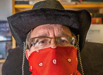 Cowboy with kerchief mask and glasses practices social distancing during the Coronavirus crisis.