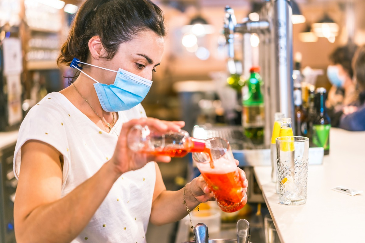 waitress with a face mask in a bar.