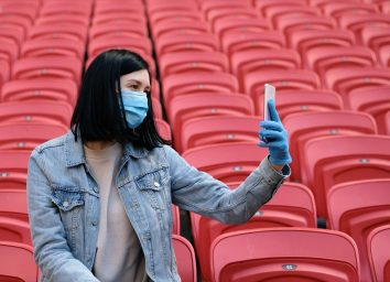 A cheerleader girl in a medical mask and rubber gloves takes a selfie or photographs on a smartphone alone in an empty stadium with red seats