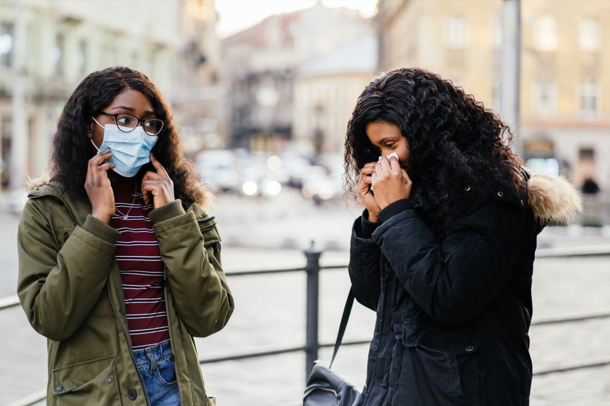 with sneezing at city street, woman without protective mask while spreading flu,cold, Covid-19