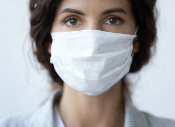 woman cover her face wearing facial medical blue mask