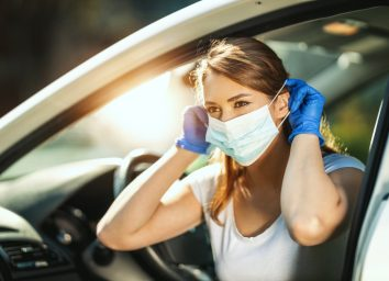 woman is putting a mask on her face, to avoid infection during flu virus outbreak and coronavirus epidemic, getting ready to go to work by car