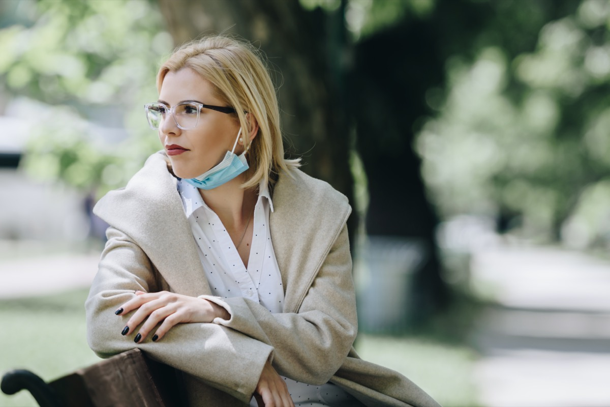 Woman with medical mask sitting