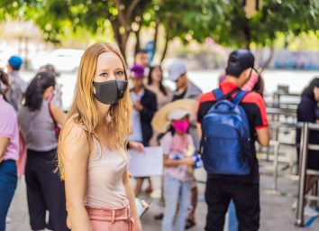 young woman wearing a hygiene protective mask over her face while walking at the crowded place