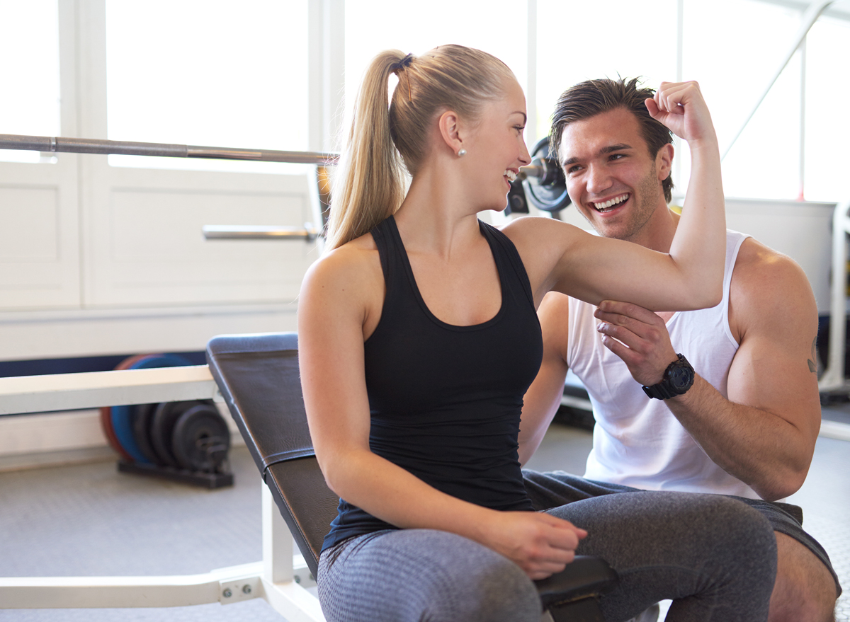 Woman flexing muscle in front of personal trainer