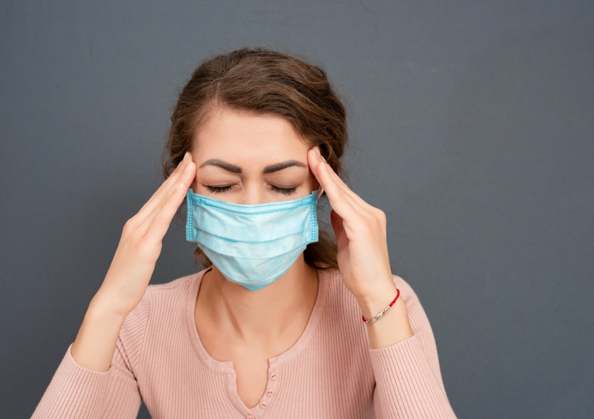 young brunette girl in medical mask holds her head