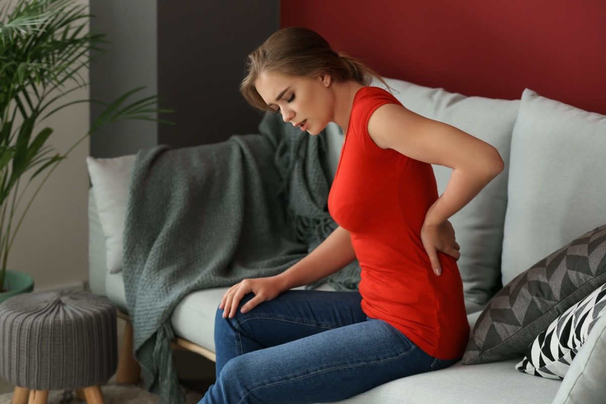 Young woman suffering from back pain while sitting on sofa at home