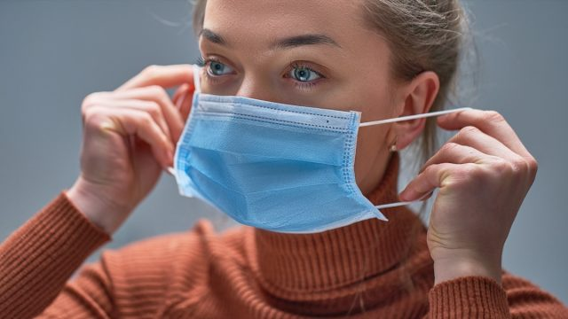 putting on medical protective mask to health protection and prevention during flu virus outbreak, epidemic and infectious diseases
