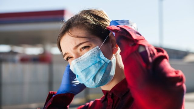 woman adjusting protective face mask,standing on petrol station parking lot