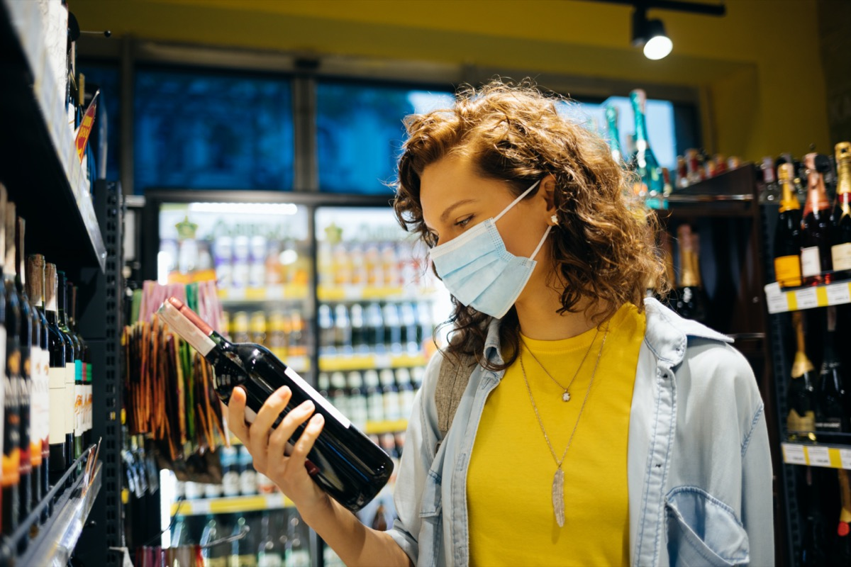 woman wearing protective face mask chooses wine in grocery store