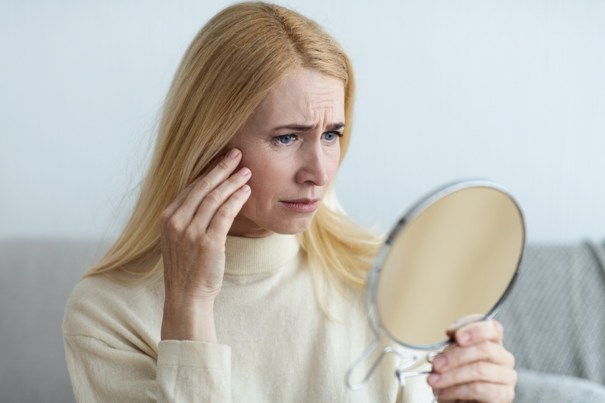 Mature Sad Woman Looking At Her Wrinkles In Mirror