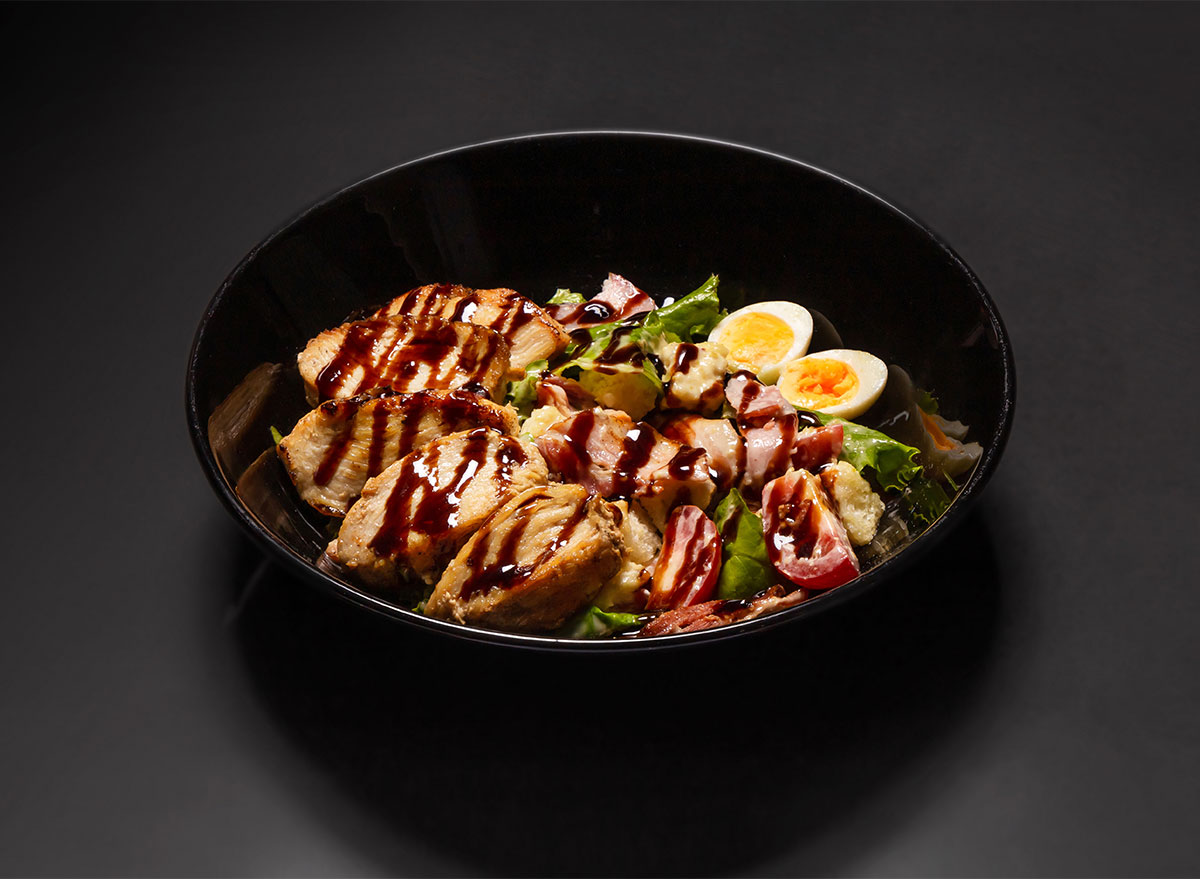 caesar salad with meat and eggs in black bowl