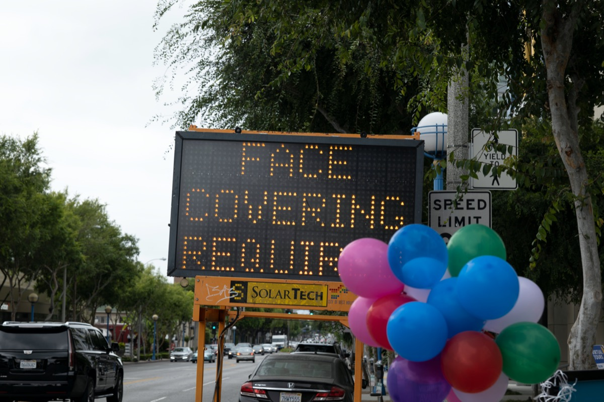 a road sign still reads Face Covering Required for coronavirus