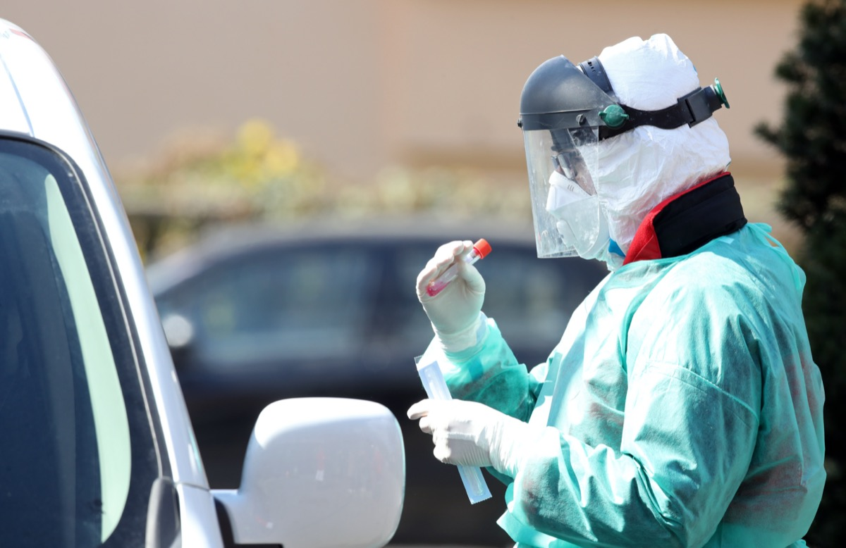 Medical staff member with mask and protective equipment performs Coronavirus nasal swabs test tubes at drive-through testing point in an effort to curb the spread of COVID-19 (novel coronavirus).