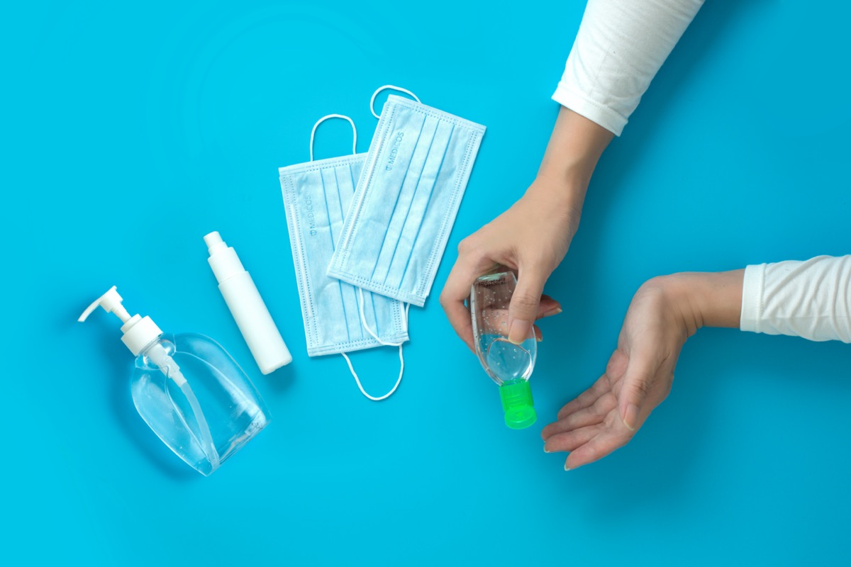 Women hands holding hand sanitizer with alcohol spray and surgical mask.