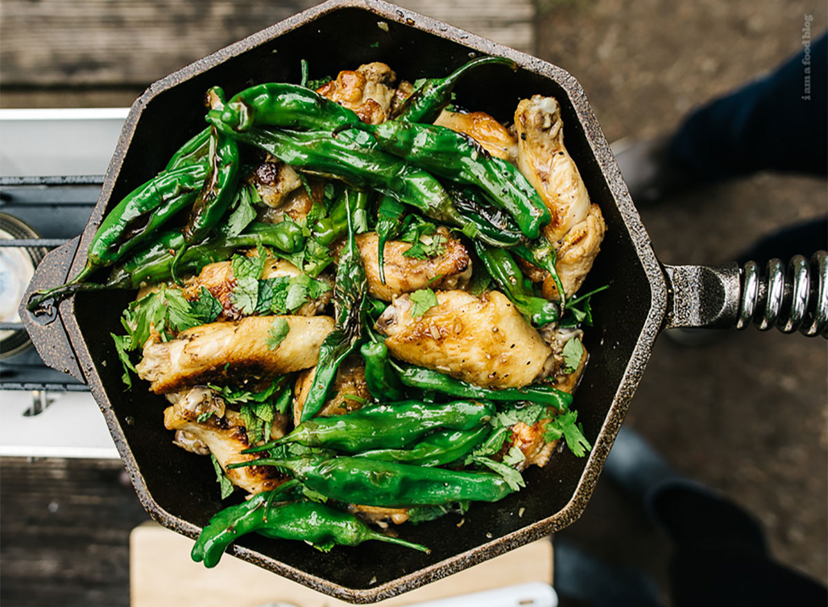 chicken wings made with fish sauce and whole shishito peppers in skillet