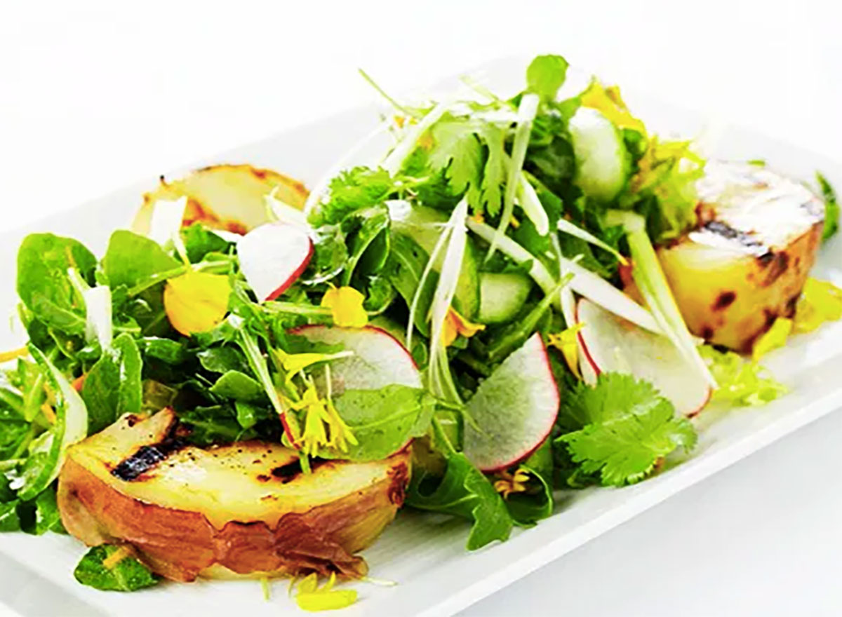 grilled pear and arugula salad on white plate