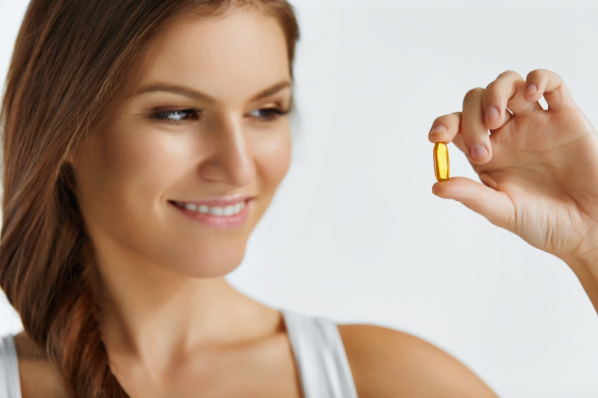 Happy Beautiful Girl With Pill With Cod Liver Oil Omega-3