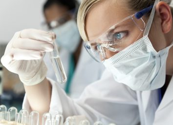 medical or scientific researcher or doctor using looking at a clear solution in a laboratory