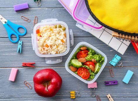 lunch boxes with kids school supplies and whole apple