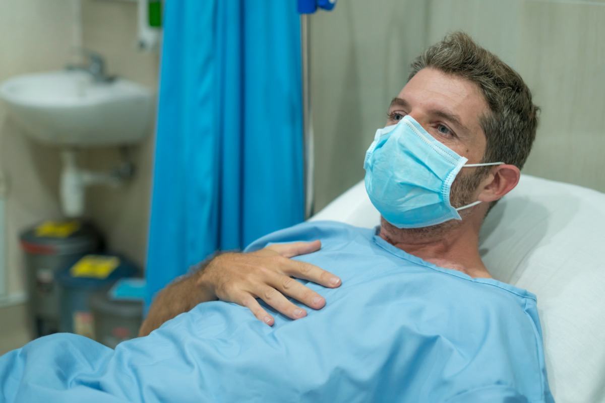 adult male in face mask receiving treatment at hospital suffering respiratory disease lying on bed
