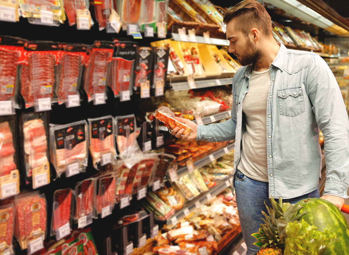 man shopping for pork bacon in meat aisle and checking the label for price