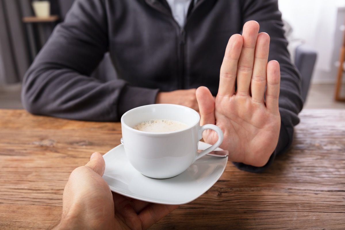 Close-up Of A Man's Hand Refusing Cup Of Coffee Offered By Person Over Wooden Desk