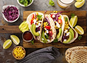 pulled pork tacos topped with avocado and cotija cheese served with lime wedges and corn