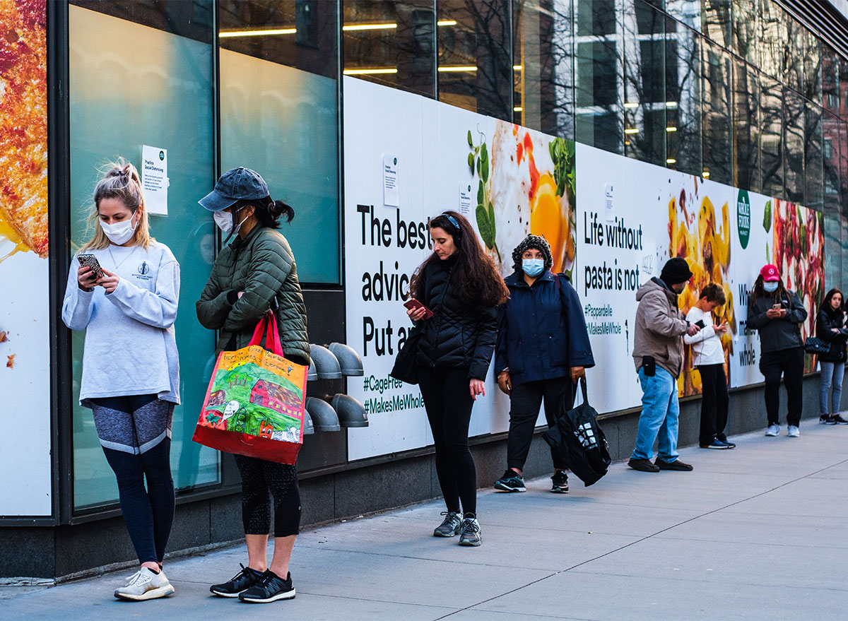 people wearing masks in line outside whole foods