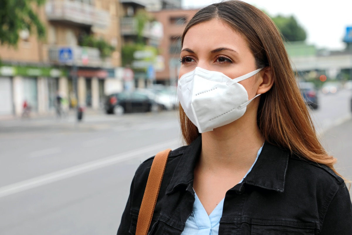 Woman in city street wearing KN95 FFP2 mask protective for spreading of disease virus SARS-CoV-2.
