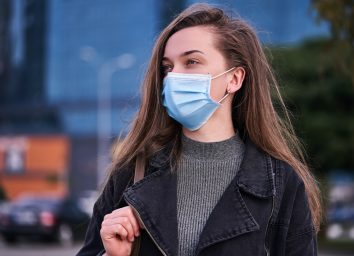 Woman wearing medical protective mask outdoors