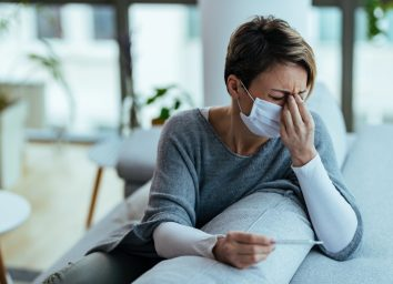 woman with face mask feeling sick and holding her head in pain while measuring temperature at home.