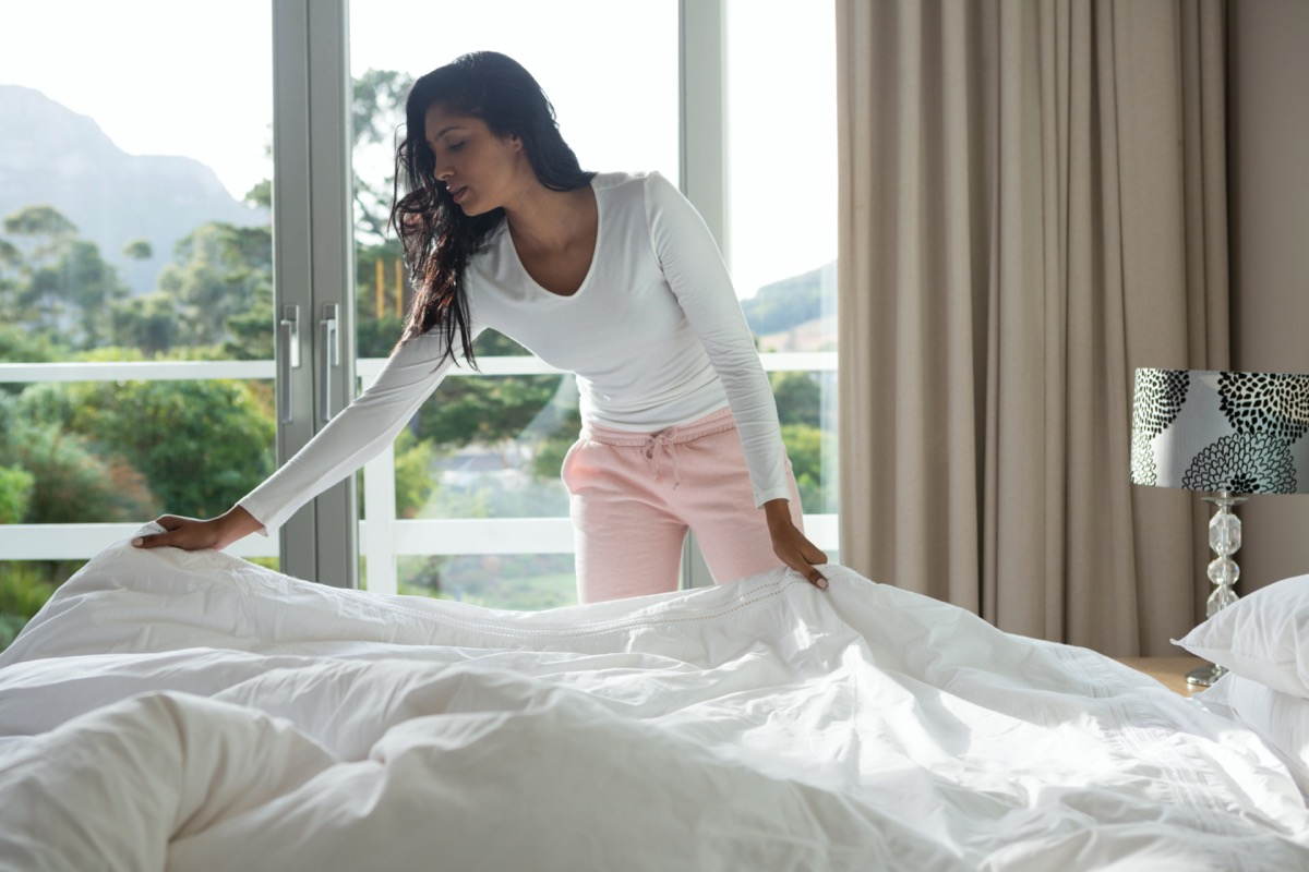 woman making bed at home.