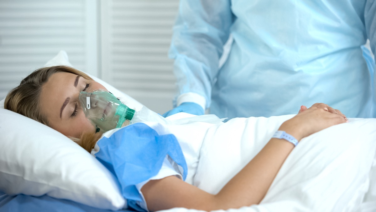 Female patient in oxygen mask sleeping, nurse standing by, surgery preparation