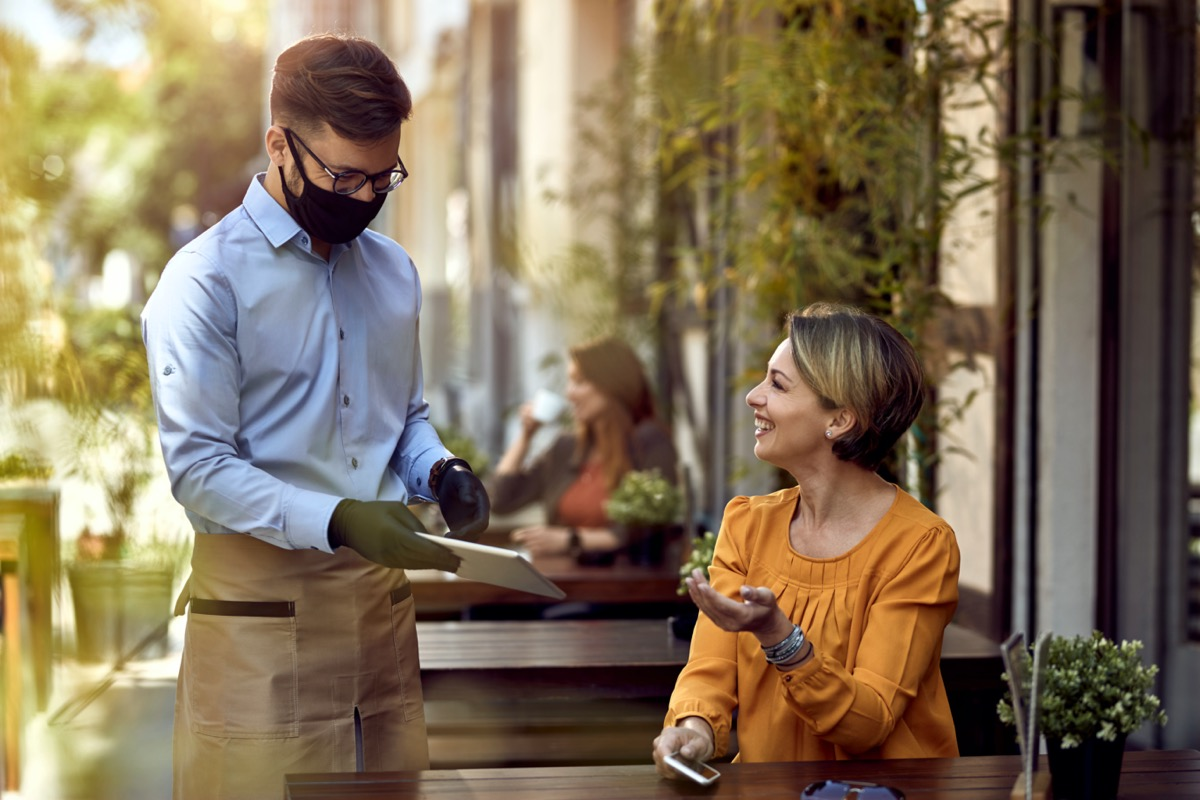 Happy waiter wearing protective face mask while showing menu on digital tablet to female guest in a cafe.