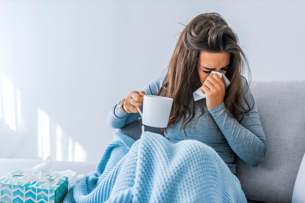 Sick woman with headache sitting under the blanket